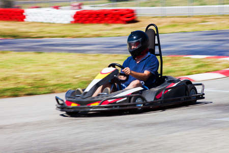 carting: man drive karting car on outdoor track