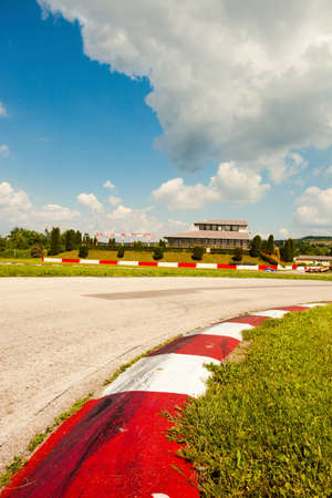 forefront: empty motor speedway with curve in the forefront