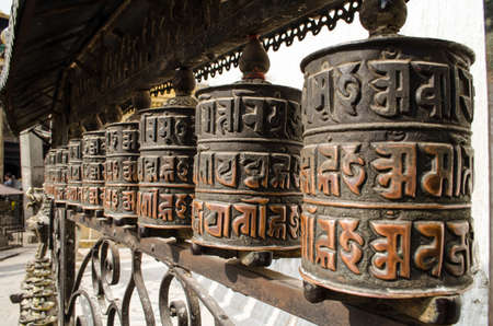 devotional: Prayer wheels are used primarily by the buddhists of tibet and Nepal, where hand-held prayer wheels are carried pilgrims and other devotees and turned during devotional activities. Stock Photo