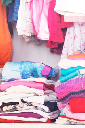 messy clothes: Wardrobe with child clothes