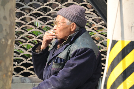 Old Chinese man smoking in Shanghai, China February 2017 Editorial