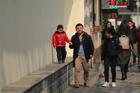 Happy Chinese family, man holding sons hand, wife looking at family, taken in Shanghai, China in February 2017 Editorial