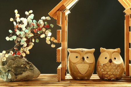 a pair of ceramic owls in a plywood miniature house
