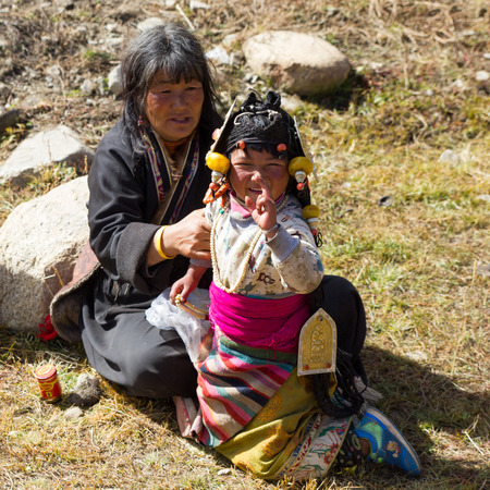 Yading, China - October 27 2016: A young girl in a traditional Tibetan costume manages a slight frown at the camera as another girl in the background looks on.