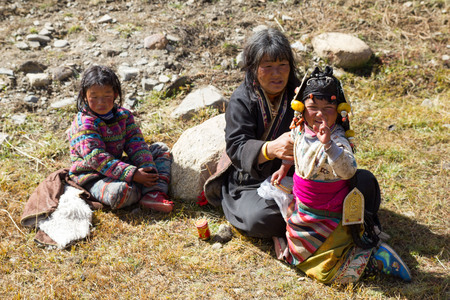 Yading, China - October 27 2015: A middle aged woman with two young girls dressed in traditional Tibetan costumes. The woman holds one of the girls as she makes a funny face at the camera. Imagens - 117944985