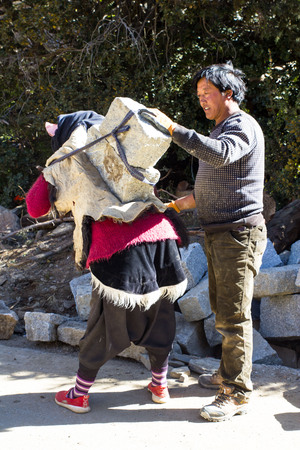 Woman laying rock slabs on the back of a woman laborer