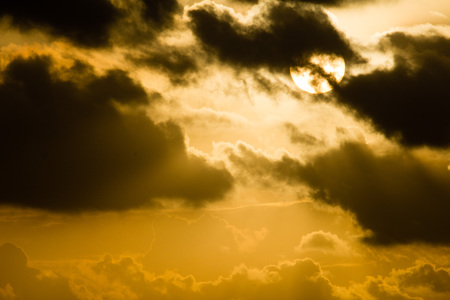 partially hidden sun behind dark clouds