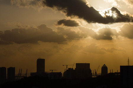 silhouette of a city beneath a dark clouds covered sun