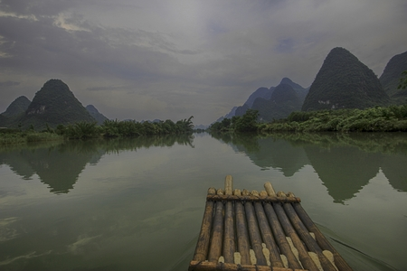 drifting on a narrow, wooden raft in a wide river with rolling hills on either side Imagens