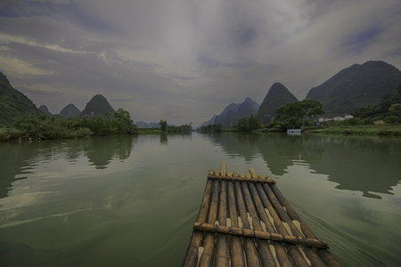 drifting on a wooden raft in a picturesque rural countryside with rolling hills on a cloudy day