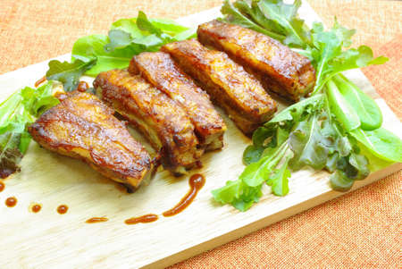 bbq sauce: Oven-roasted pork spareribs with BBQ sauce served with fresh organic vegetable on wood chopping block.