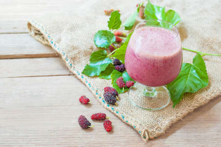 booster: A glass of mulberry yogurt smoothie, a beautiful booster smoothie, on burlap and wood background.
