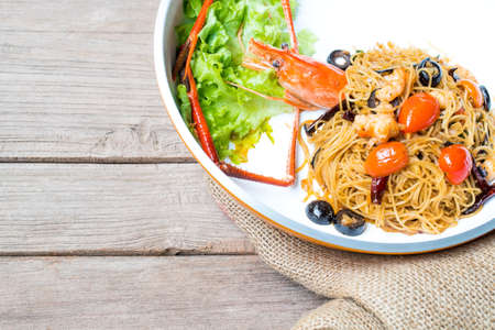 angel hair: Angel hair pasta with giant prawn, olives, tomatoes, and chilli on burlap and old wood background, rustic style Stock Photo