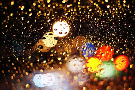 windscreen: Abstract night city light and bokeh through car windscreen covered in rain, defocussed background Stock Photo