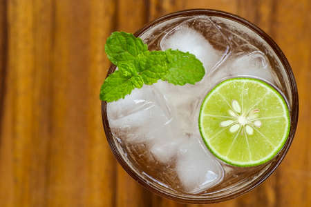 Top view of fresh cocktail with lime slice and mint on wood background. Mojito cocktail. Virgin mojito. Non-alcoholic mojito mocktail. Margarita cocktail. Fresh lemonade. Honey lemon soda.