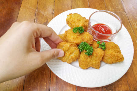 nugget: Hand picking chicken nugget in white plate on wood background
