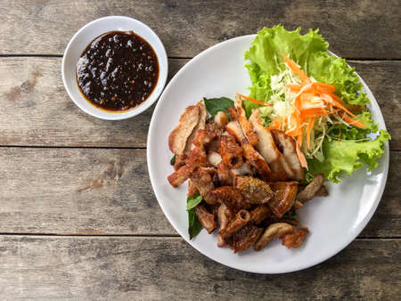 northeastern: Street Thai food, roasted pork including small pig intestines and charcoal-boiled pork neck served with spicy dip and vegetable on old wood grungy background.  Stock Photo