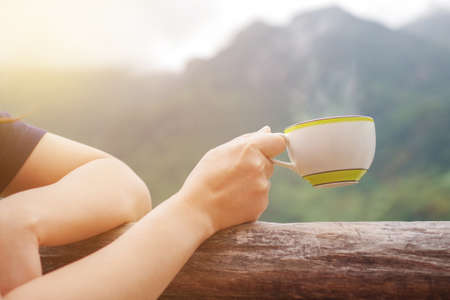 Morning cup of hot drink, coffee or tea cup in female hand on mountain view blurred background and morning sunlight. Travel and relaxation concept.