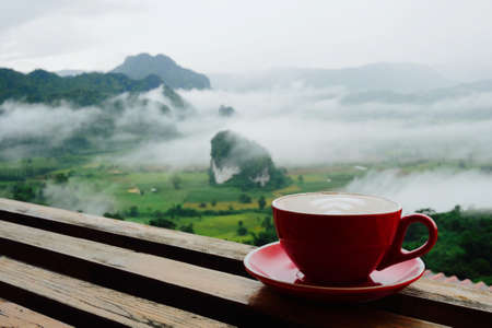 Hot coffee latte cappuccino in red cup on wooden terrace with beautiful scenic view nature background of misty morning mountain in Phayao, Thailand.