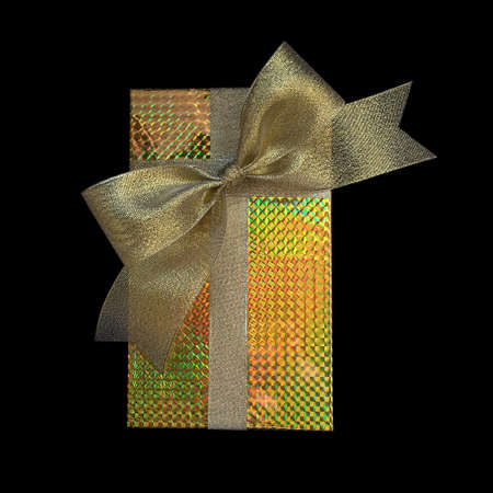 Gift box wrap and ribbon with gold foil hologram wrapping paper and big bow golden ribbon isolated on black background