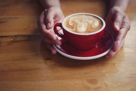 Hot coffee latte cappuccino in red cup and saucer with beautiful latte art milk foam on baristas hands holding serving on wood table background. 스톡 콘텐츠