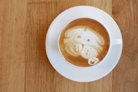 Top view of hot coffee latte cup with cute pug dog latte art milk foam on light wood texture background. 스톡 콘텐츠