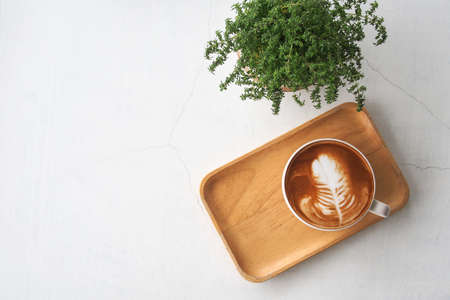 Top view of hot coffee latte cup with leaf shaped latte art milk foam on wooden tray and green small potted plant on white cracked concrete table background. Banco de Imagens - 130160601