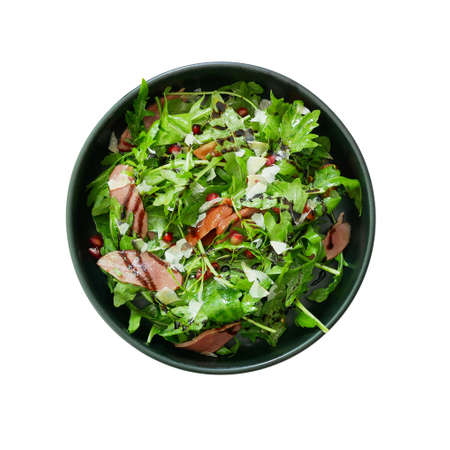 Top view of fresh green vegetable salad with sliced smoked duck and red pomegranate seeds and Parmesan cheese shaved in black bowl, healthy food dish isolated on white background with clipping path.