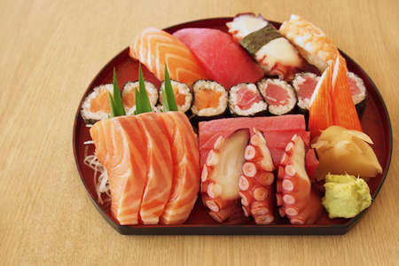 Japanese food sashimi ( (raw sliced fish, octopus, etc.) and sushi set served with fresh wasabi paste and pickled ginger on light brown table background. Фото со стока