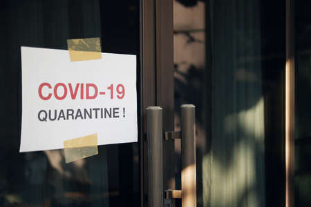 Self quarantine door sign due to novel Coronavirus COVID-19 pandemic, warning texts on white paper stick on home front door in self isolation time to stay at home for virus protection and prevention.