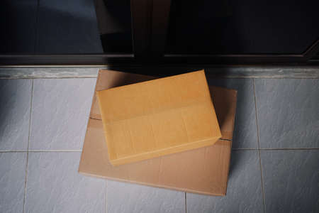 Safe contactless delivery courier services to door during the Coronavirus (COVID-19) pandemic, top view of delivered cardboard boxes packages on porch outside home front door.