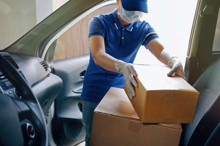 Delivery services courier during the Coronavirus (COVID-19) pandemic, courier wearing medical mask and latex gloves for safety protection from virus infection working with cardboard boxes on van seat. Foto de archivo