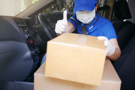 Delivery services courier during the Coronavirus (COVID-19) pandemic, courier driver wearing medical face mask and latex gloves showing thumbs up with cardboard boxes packages on delivery van seat.