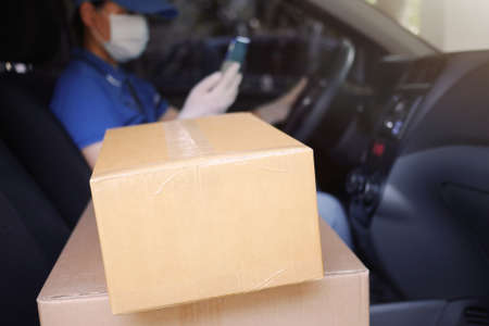 Delivery services courier during the Coronavirus (COVID-19) pandemic, cardboard boxes on delivery van seat with courier driver in blurred background wearing medical mask and latex gloves holding phone Foto de archivo