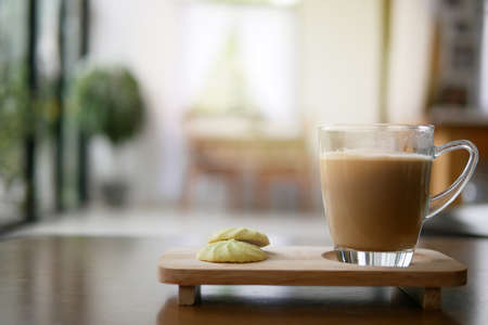Morning coffee cup with two pieces of cookies on wood table in home blurred background, drinking coffee before start working from home concepts.