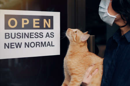 """Reopening for business adapt to new normal in the novel Coronavirus COVID-19 pandemic. A cat with their owner person wearing mask in front of business shop with open sign """"OPEN BUSINESS AS NEW NORMAL"""