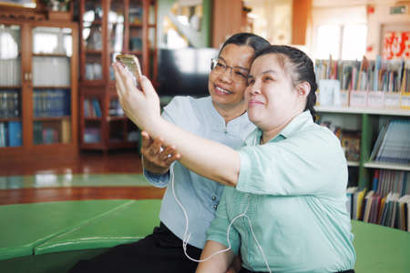 Asian young blind woman disabled person taking selfie using smart phone with her senior colleague woman in creative workplace Banque d'images