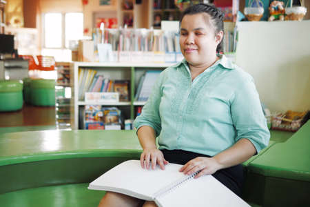 Portrait of Asian young blind woman disabled person reading Braille book in creative workplace