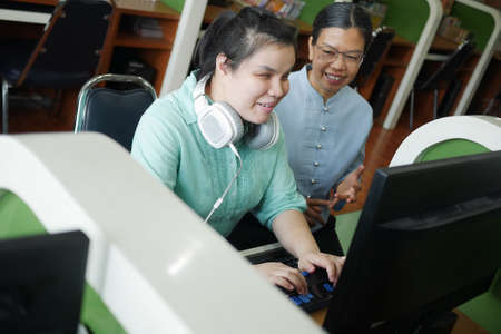 Asian young blind woman with headphone using computer with braille display assistive device discusing with senior colleague woman in workplace.