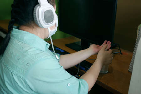 Disability blind person with headphone wearing face mask applying alcohol gel hand sanitizer on hands before using computer with braille display amid Coronavirus (COVID-19) pandemic. Banque d'images