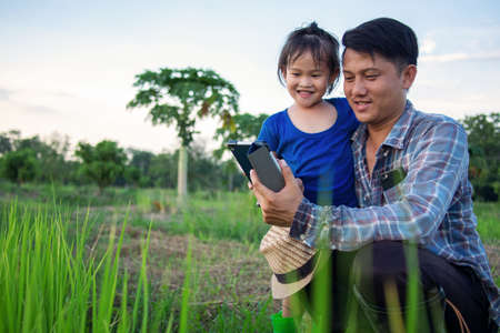 Asian smart farmer father with his happy little girl daughter using digital tablet outdoors in family organic farm. Archivio Fotografico