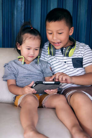 Asian children with headphones using tablet on sofa in countryside home, older brother telling his little sister stories on tablet screen and teaching how to play video and video call. Archivio Fotografico