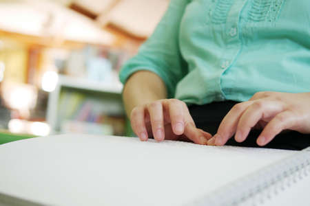 Close-up of blind person woman hands reading Braille book studying in creative library.