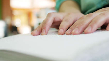 Close-up of blind person woman hands reading Braille book studying in creative library. Braille is a system of raised dots that can be read with the fingers by people who are blind or low vision.