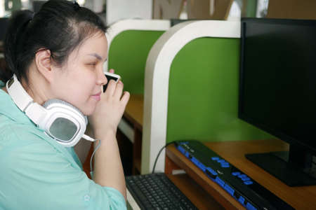 Asian young blind person woman with headphone using smart phone with voice assistive technology for disabilities persons in workplace with computer and braille display on table. Imagens