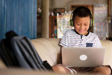 Online remote learning, distance education and homeschooling concepts. School kid Asian preteen boy in headphone using laptop computer on couch in rustic rural home during COVID-19 pandemic. Imagens