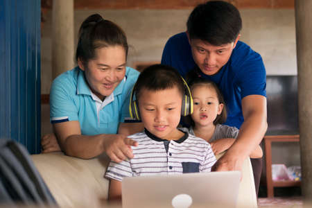 Homeschooling child boy in headphone using laptop computer with happy Asian family togetherness in rural home, parents helping kid with homework during COVID-19 pandemic. Imagens