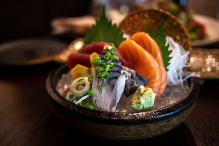 Close-up of Japanese food mixed Sashimi dish on blurred background, thinly sliced raw fish seafood served on ice with a little bit of wasabi seasoning and ornamental vegetables. Imagens