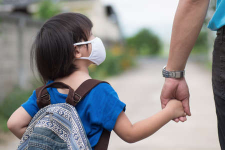 Little girl with backpack wearing cloth face mask hand in her father's hand waiting for school bus, back to school amid Coronavirus (COVID-19) pandemic. 写真素材