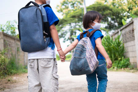 Little girl with backpack wearing cloth face mask holding her older brother's hand walking to school in rural scene. Return to school amid Coronavirus COVID-19 pandemic concept. 写真素材